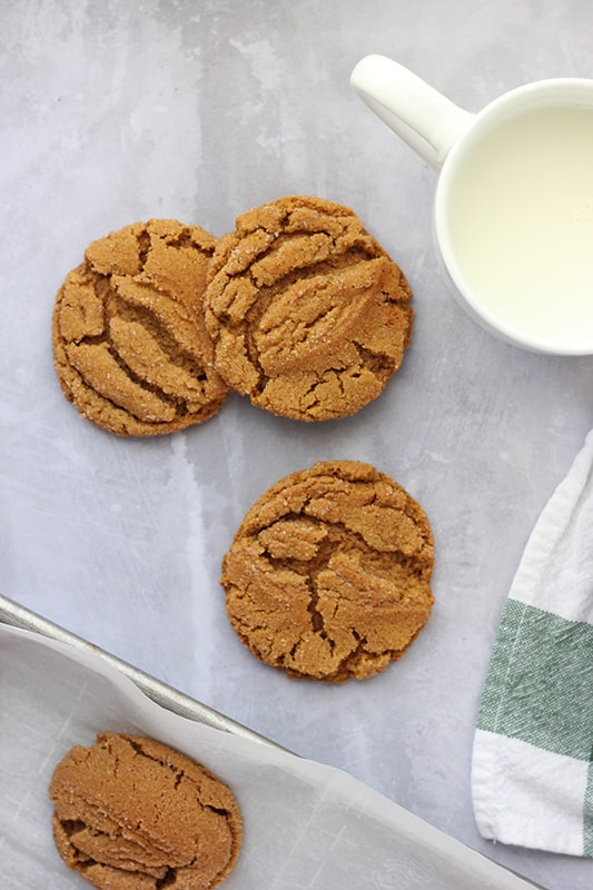 stack of gingersnap cookies with glass of milk