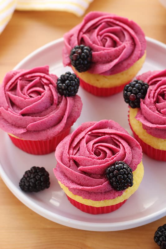 Blackberry frosting on top of lemon cupcakes displayed on white plate