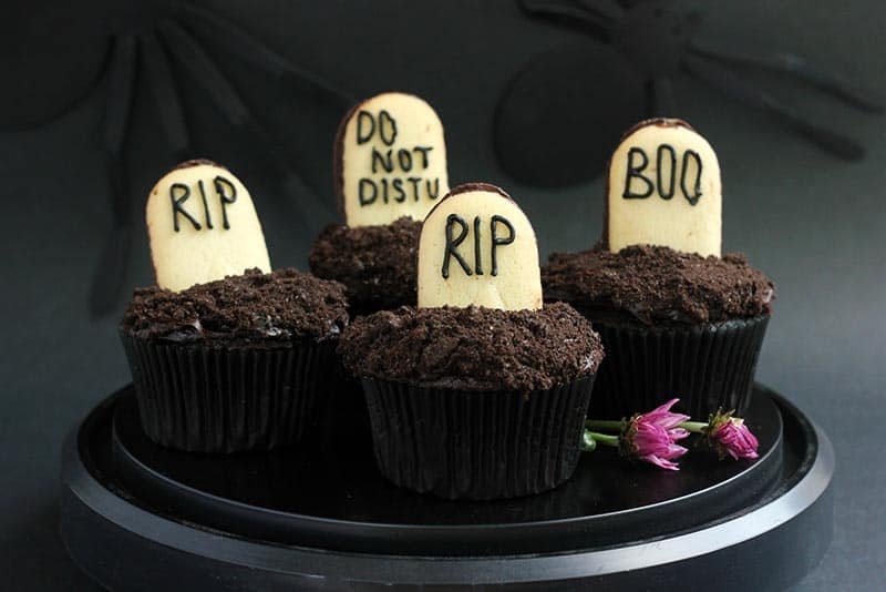 Graveyard cupcakes on a black plate.