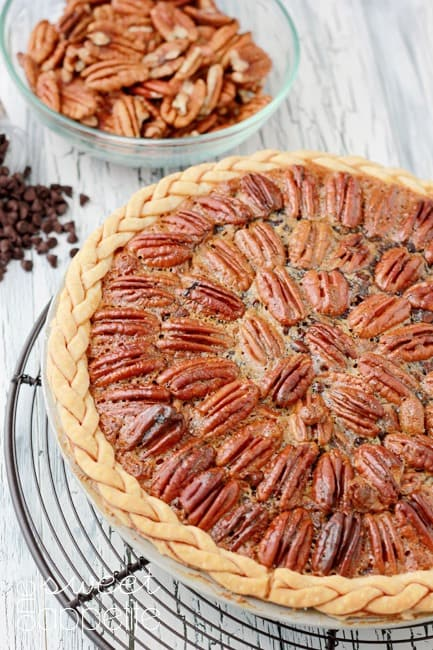 Pecan pie on a white wood table with a small bowl of pecans and spilled chocolate chips
