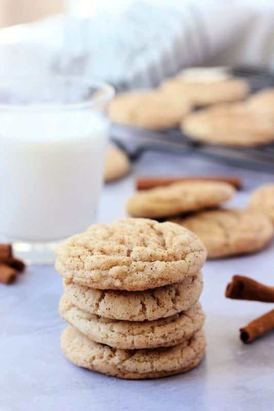 Snickerdoodle Cookies stacked on white table with glass of milk