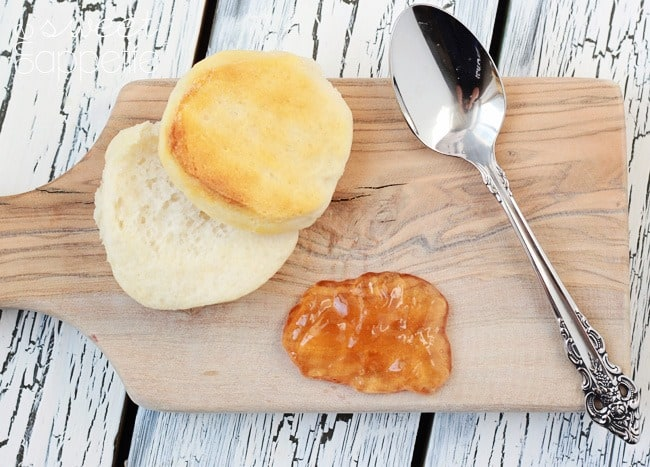Biscuit split in half on cutting board with apple jelly.