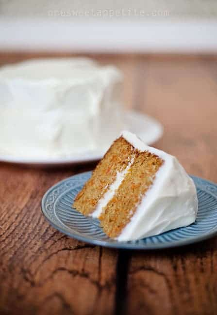 carrot cake with cream cheese frosting on blue plate