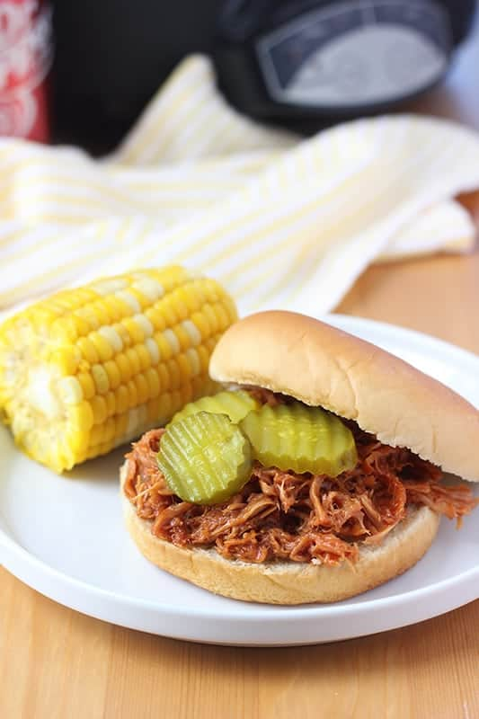 Pulled Pork Sandwich on white plate with pickles and side of corn on the cob