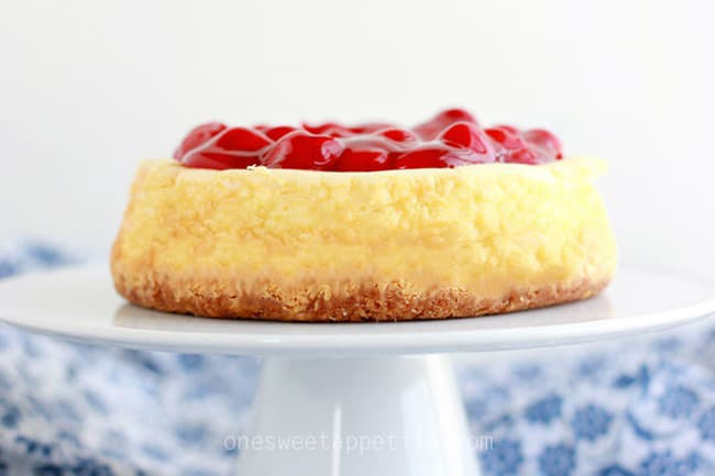 Cheesecake on cake stand with cherry topping