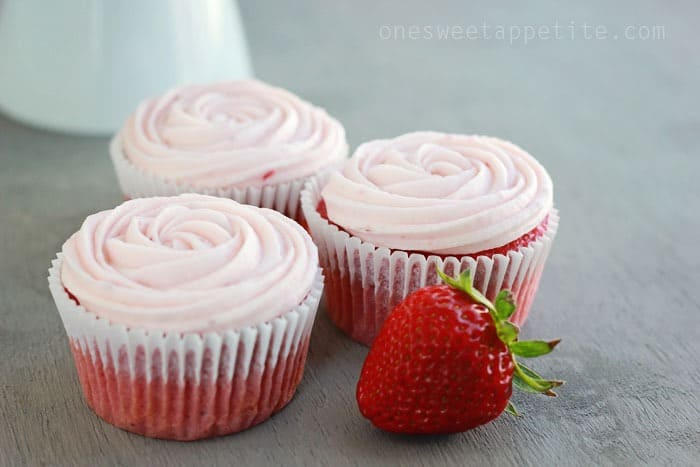 three strawberry cupcakes with a fresh berry on grey table