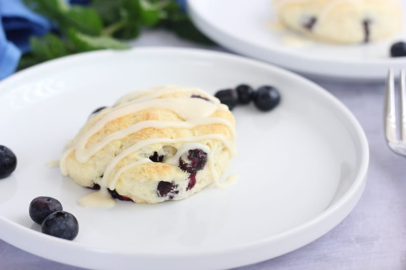 blueberry biscuit on a white plate with berries