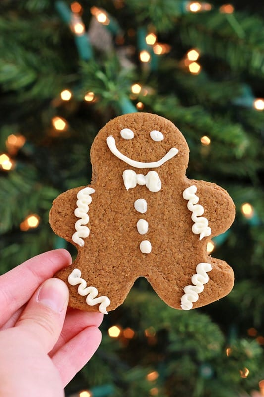 Single gingerbread man held in front of a Christmas tree