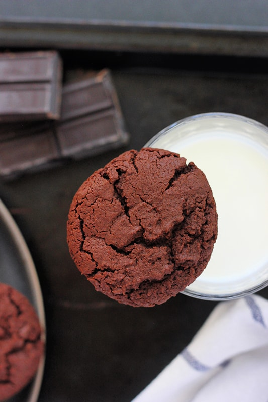 Chocolate cookie balanced on top of a glass of milk