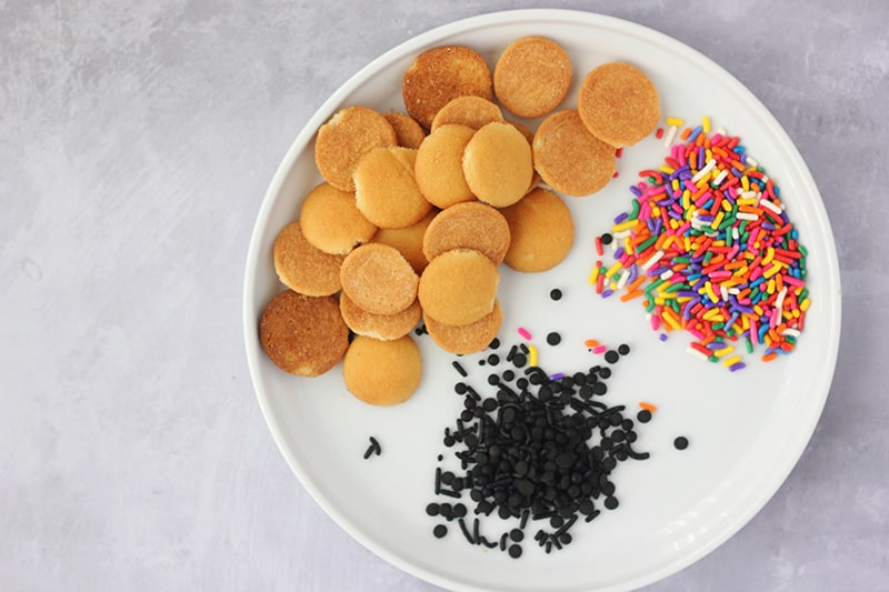 Mini vanilla wafers, rainbow and place sprinkles on white plate