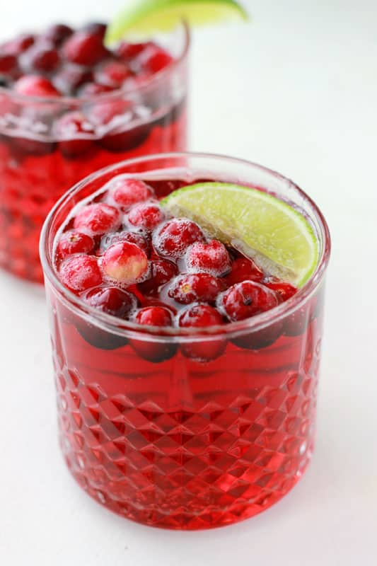 cranberry and champagne in two glasses with frozen cranberries