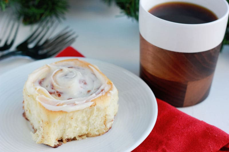 cinnamon roll on a white plate with a cup of coffee in the background
