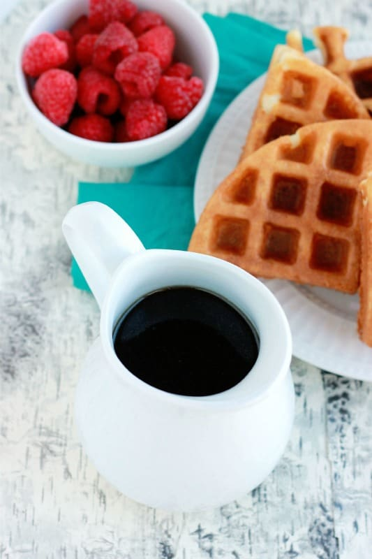 maple extract in cup with waffles and raspberries