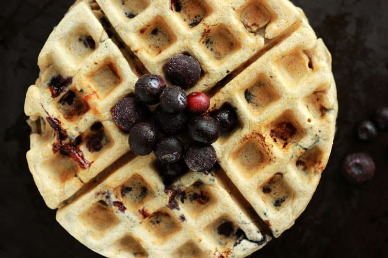 Blueberry waffle topped with extra blueberries.