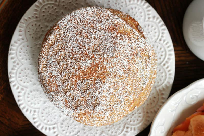 gingerbread pancakes stacked on white plate and dusted with powdered sugar