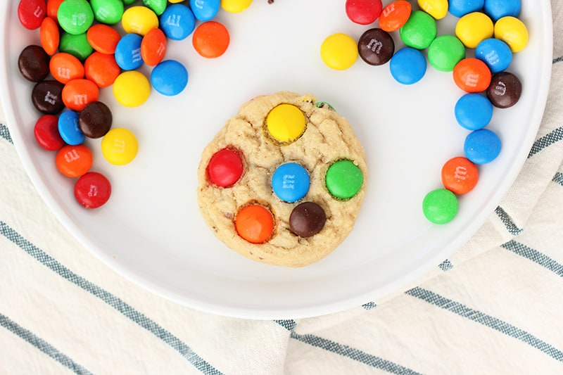 Soft and Chewy M&M Cookie on a white plate with candies