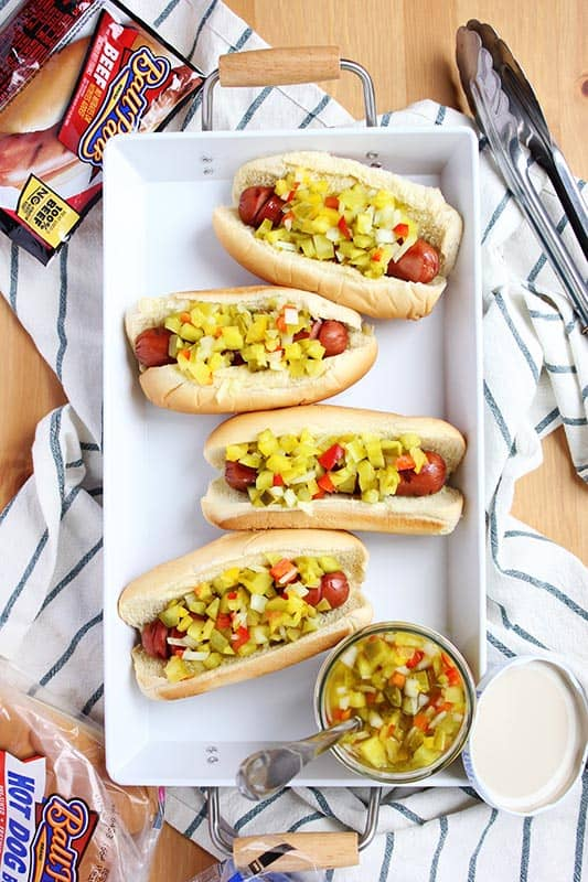 white platter with hot dogs in buns topped with relish