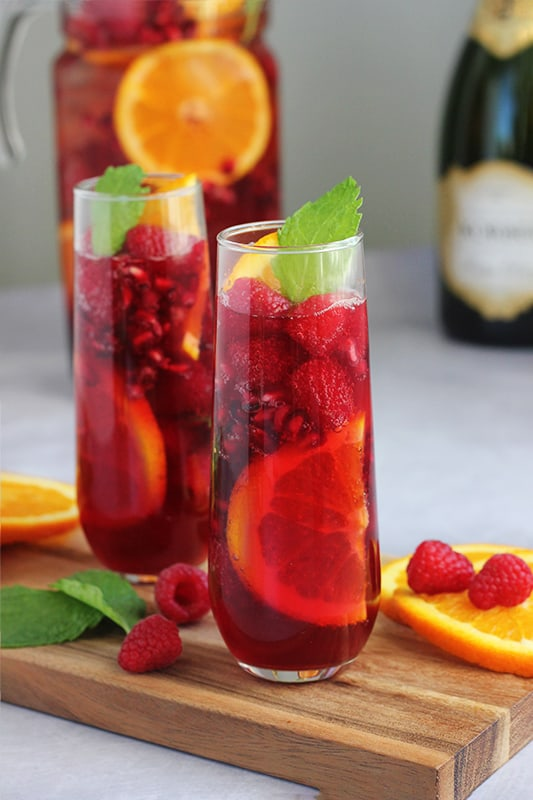 Sparkling Holiday Punch in two glasses with mint and orange slices