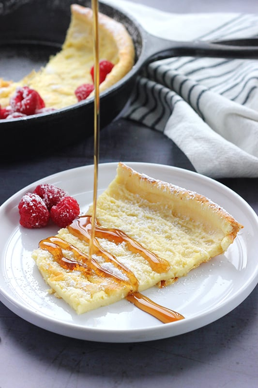 slice of puff pancake with syrup being drizzled