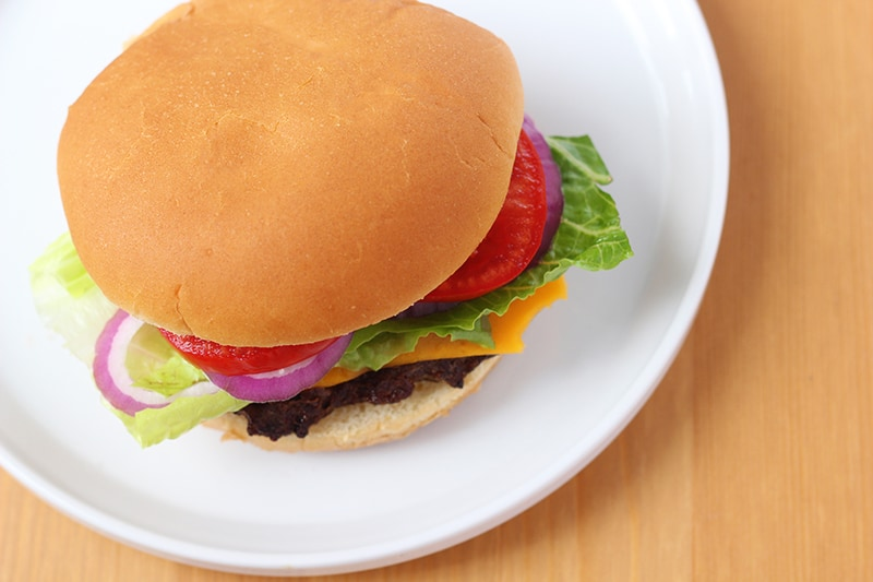 Cheeseburger on a white plate with lettuce tomato and onion