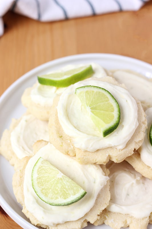 Coconut cookies stacked on a plate with lime slices