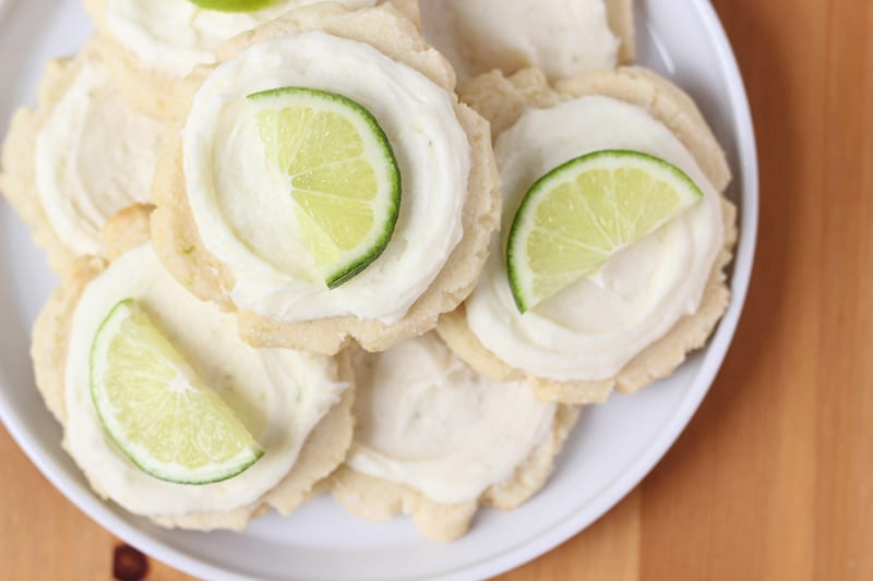 Frosted sugar cookies on a white plate with slice of lime