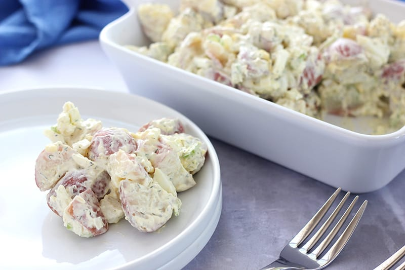 Potato salad on white plate with forks