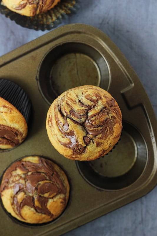 nutella swirl muffin on top of muffin pan
