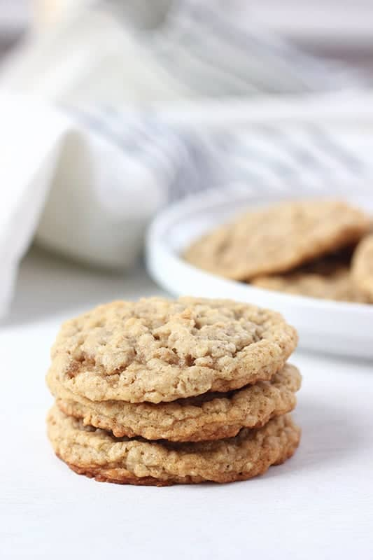 oatmeal cookies stacked in front of a plate with cookies