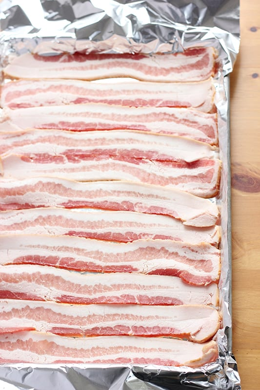 uncooked bacon layered on a baking tray