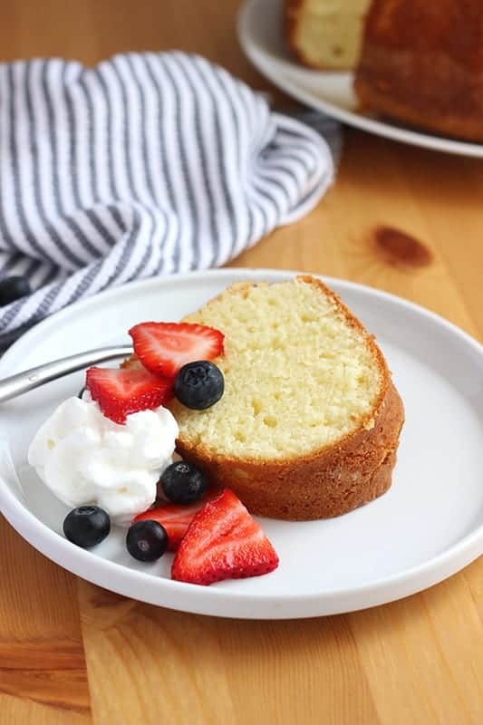 slice of pound cake with fresh berries and whipped cream on white plate with fork
