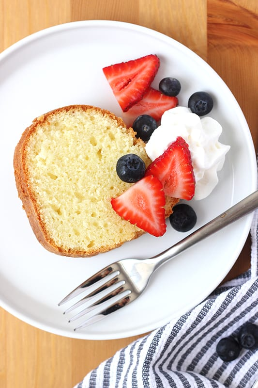slice of pound cake with fresh berries and whipped cream on white plate