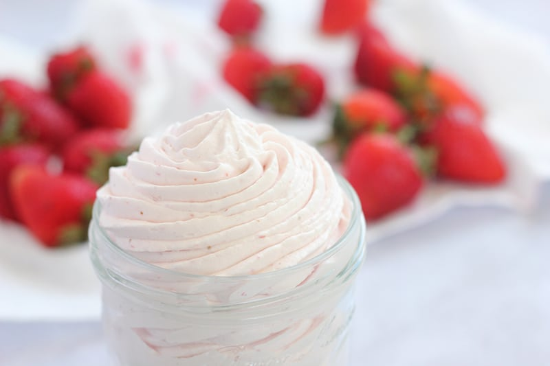 Whipped cream in jar with strawberries in background