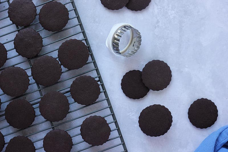 chocolate crisp cookies on cooling wrack with round cookie cutter