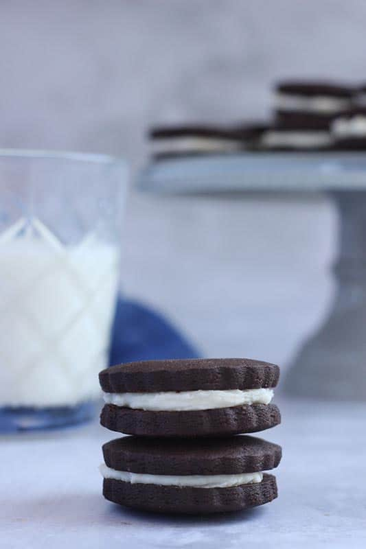homemade oreo cookies stacked with glass of milk