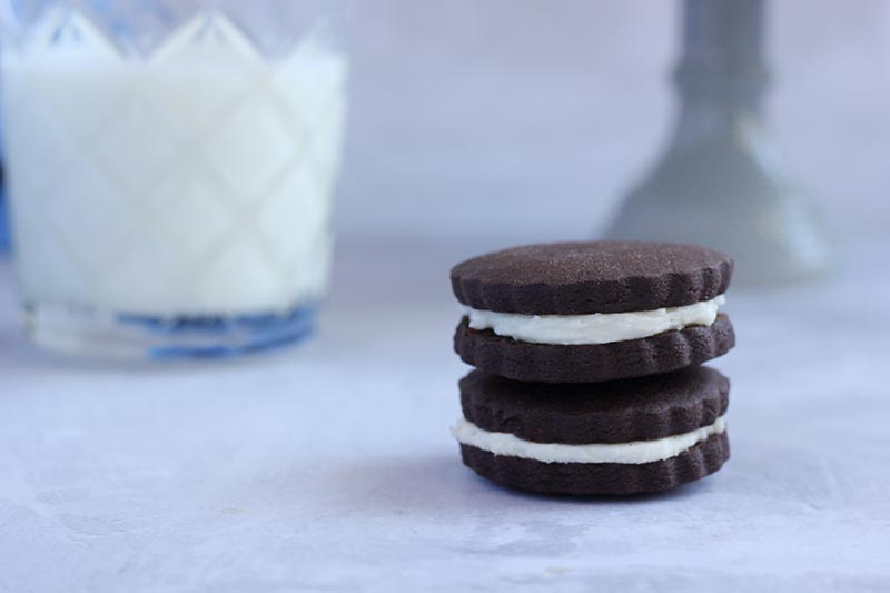 Two homemade oreo cookies stacked with glass of milk