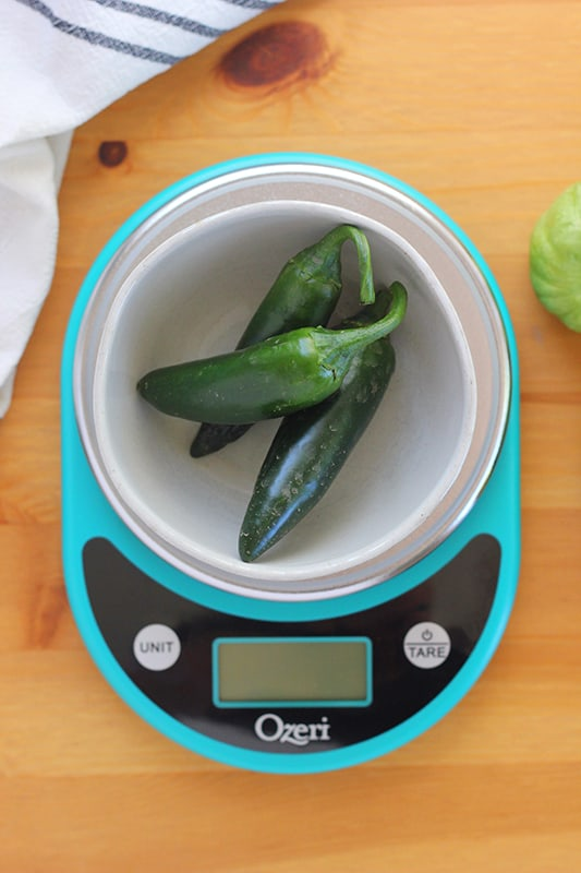 fresh jalapenos in a bowl on top of a blue kitchen scale