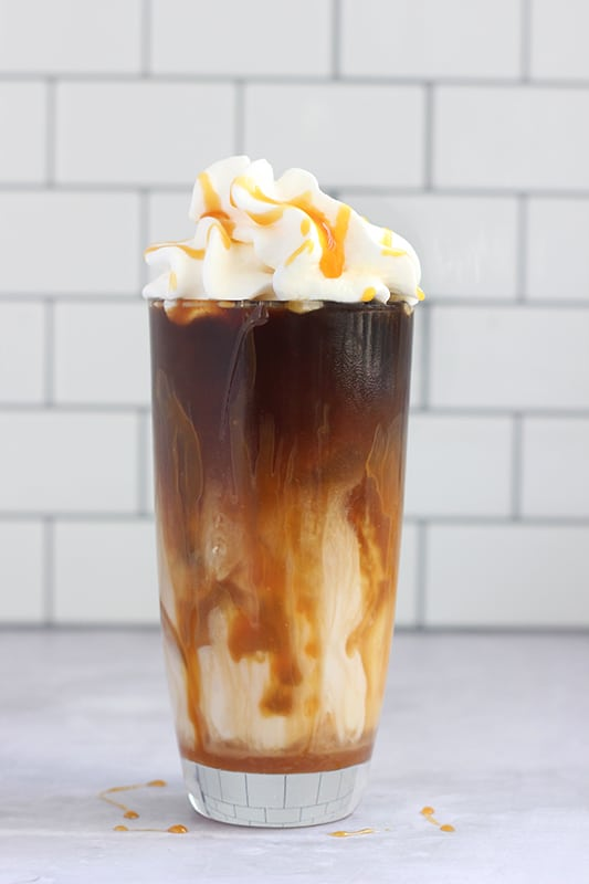 iced coffee with cream topped with whipped cream and caramel