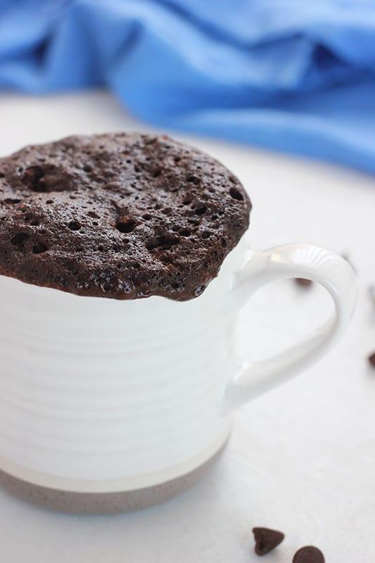 chocolate mug cake oozing over the edge of a white mug