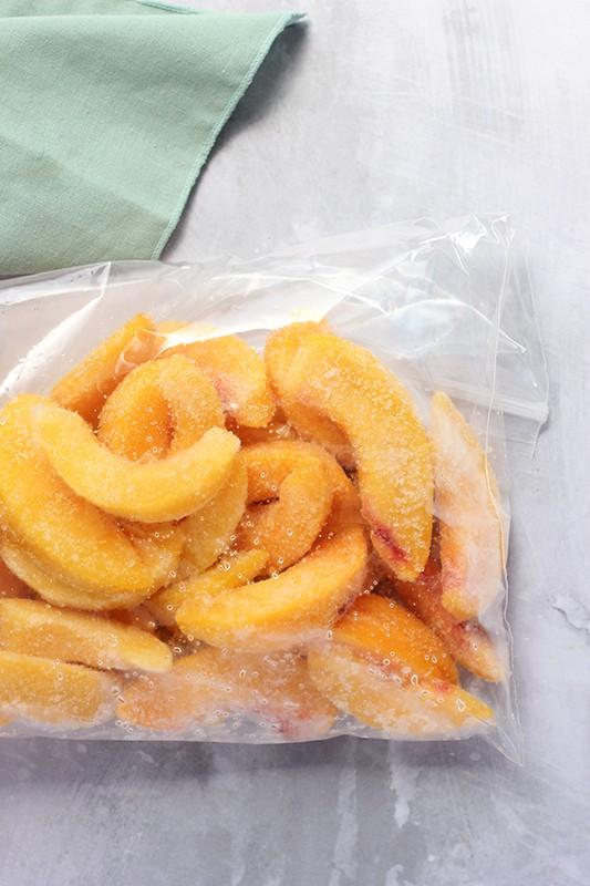 frozen peach slices in zip top bag on table top