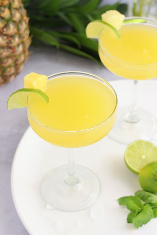 two pineapple margaritas in glasses with slices of lime hanging off the side of the cups