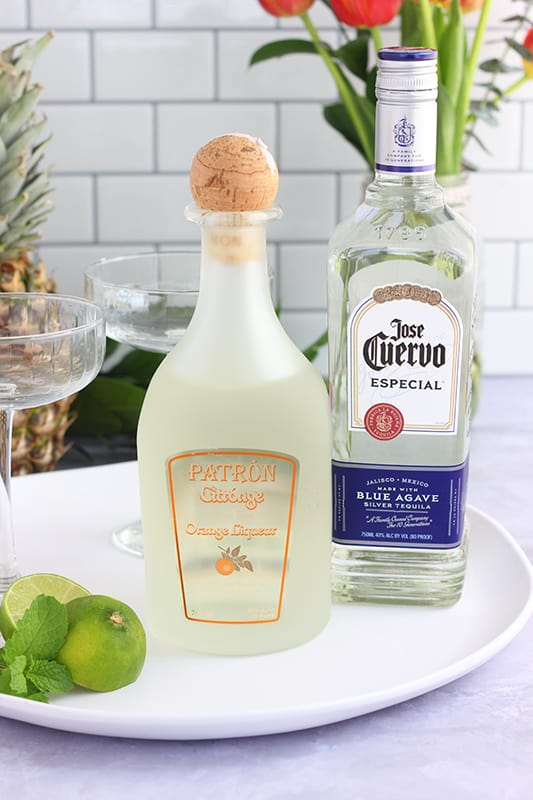tequila, orange liquor, and limes on a white serving tray