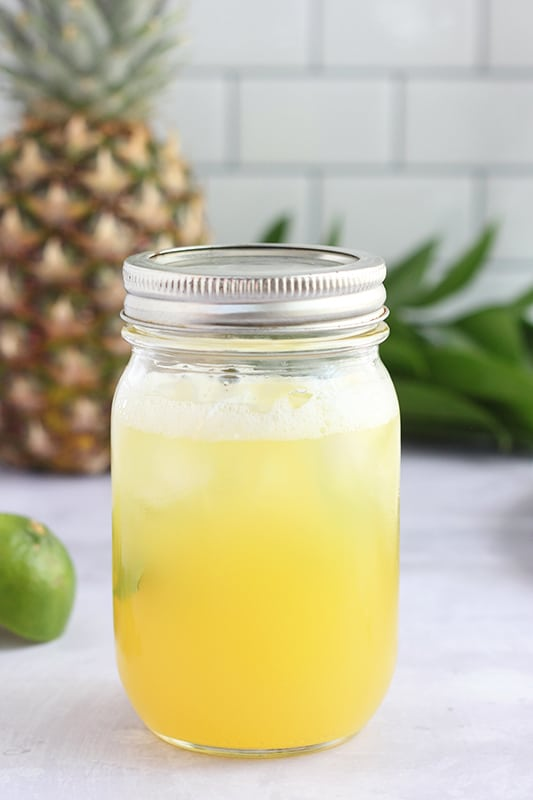 pineapple margarita ingredients inside a sealed mason jar