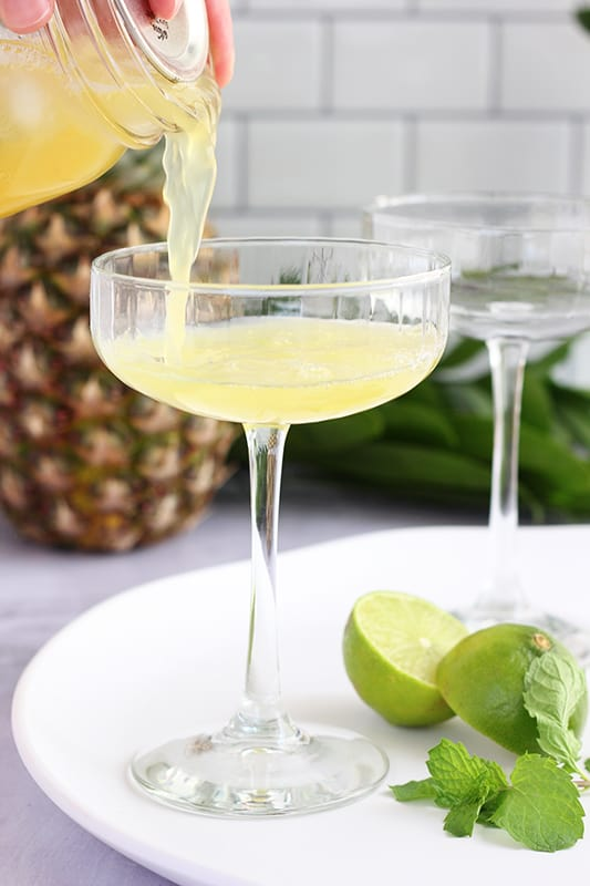 pineapple margarita being poured into margarita glass on white tray