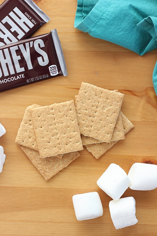 graham crackers, chocolate bars, and marshmallows laid out on tabletop