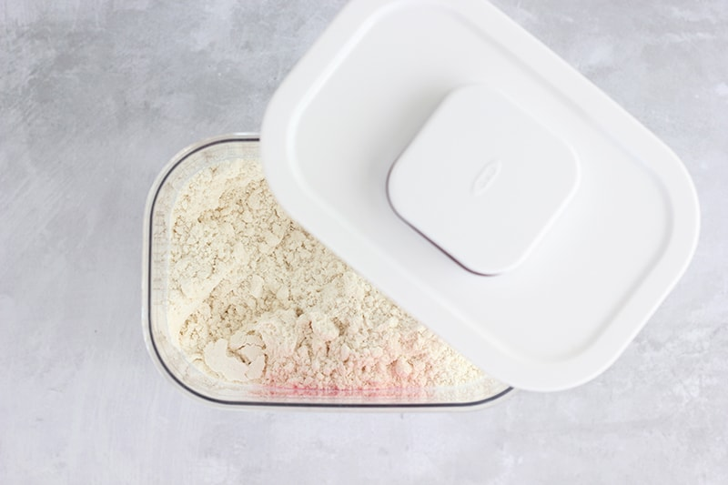 Pancake mix inside clear container with white lid ajar