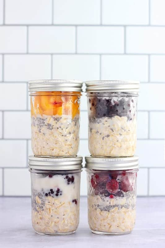four mason jars stacked and filled with overnight oatmeal and fruit