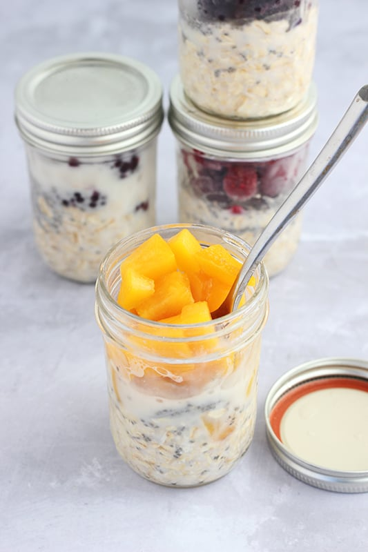 overnight oats topped with peaches in mason jar
