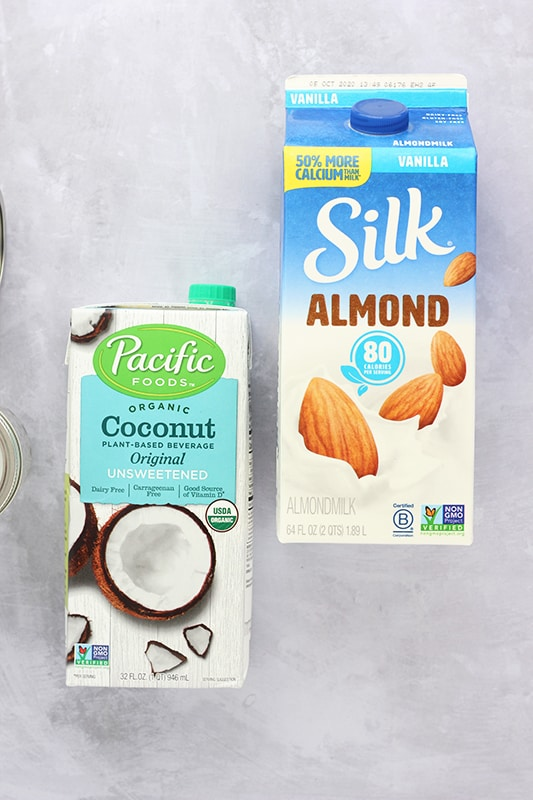 almond milk container and coconut milk container on white counter