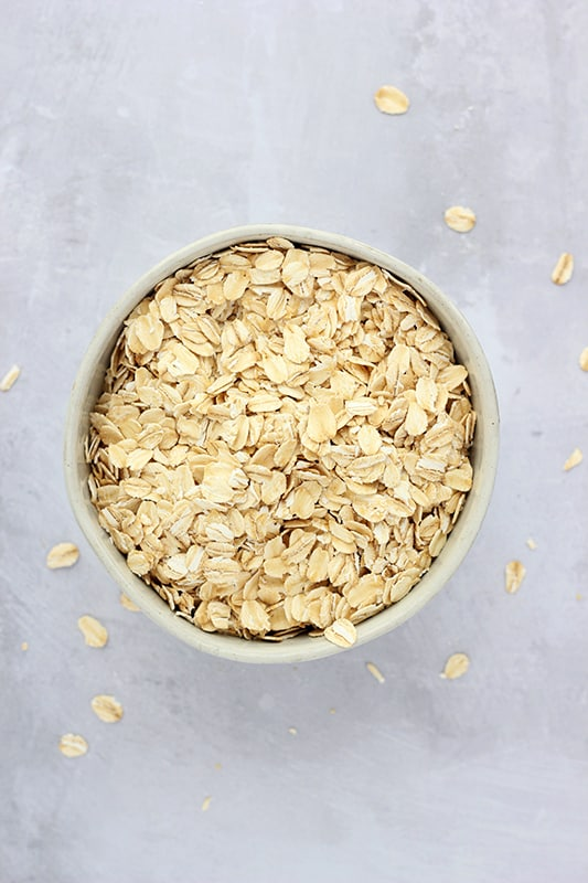 rolled oats in off white bowl on white counter top